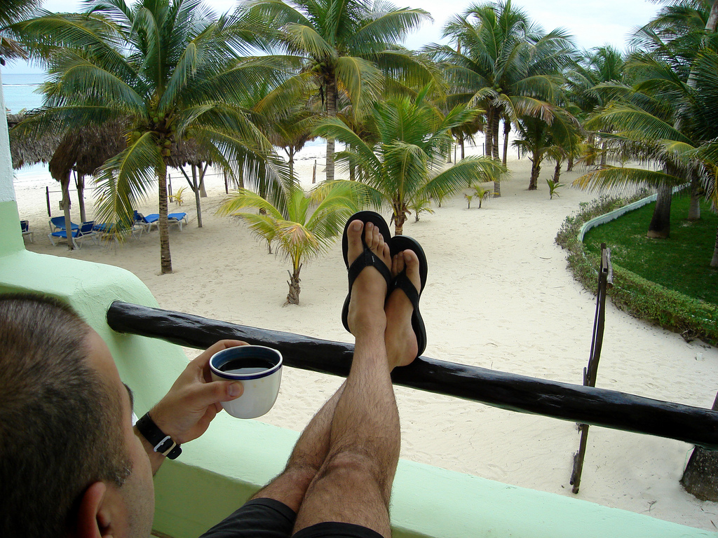A man drinking tea with his feet up looking out over sand and palm trees