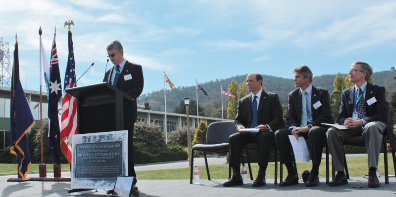 CDSCC Director Ed Kruzins speaking at ceremony with three other guests sitting