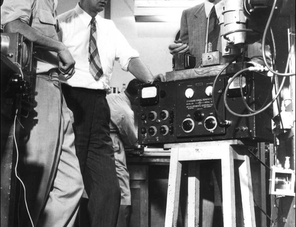 Three engineers in a 1940s laboratory looking at radio equipment.
