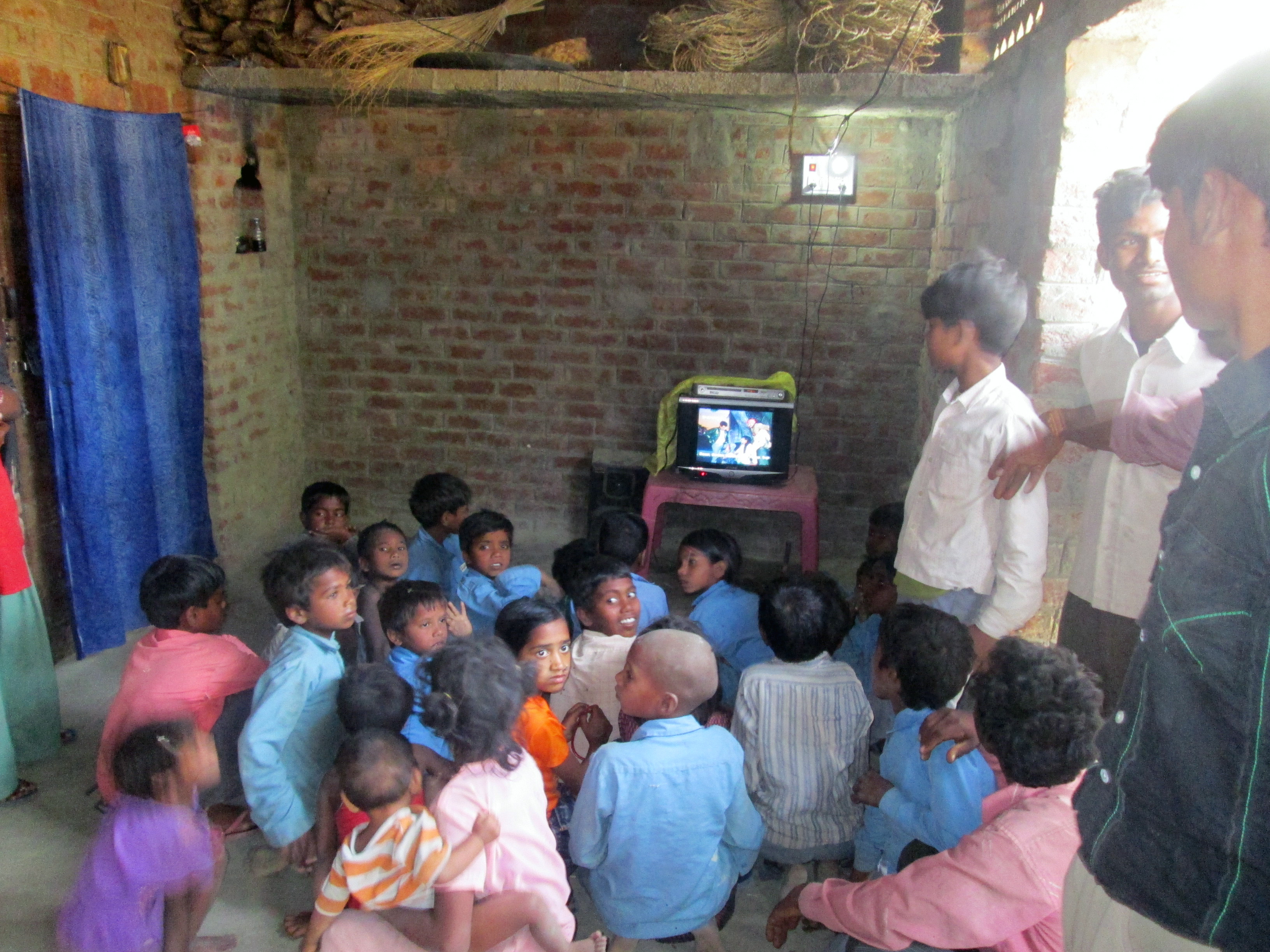 Locals from a village in the Uttar Pradesh state in northern India watch television under the glow of a light bulb, both powered by our new biomass power station.