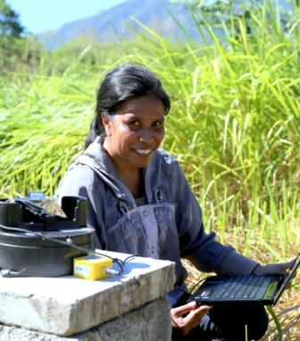 A woman using a laptop in the field.
