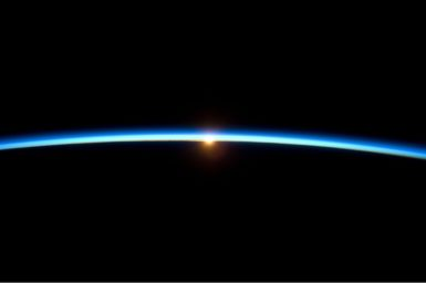 A thin blue arc separating two areas of black.