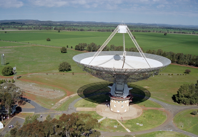 The Parkes radio telescope standing in green paddocks, seen from the air.