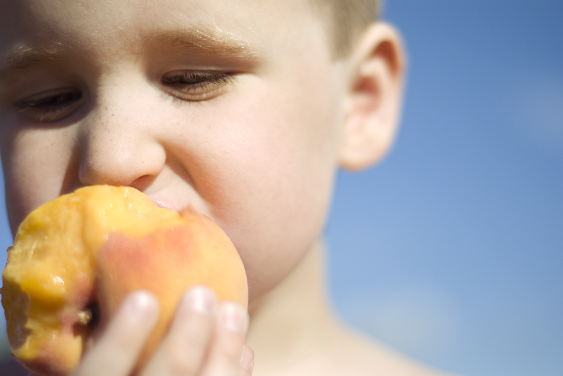 Boy biting into peach with blue sky in the background