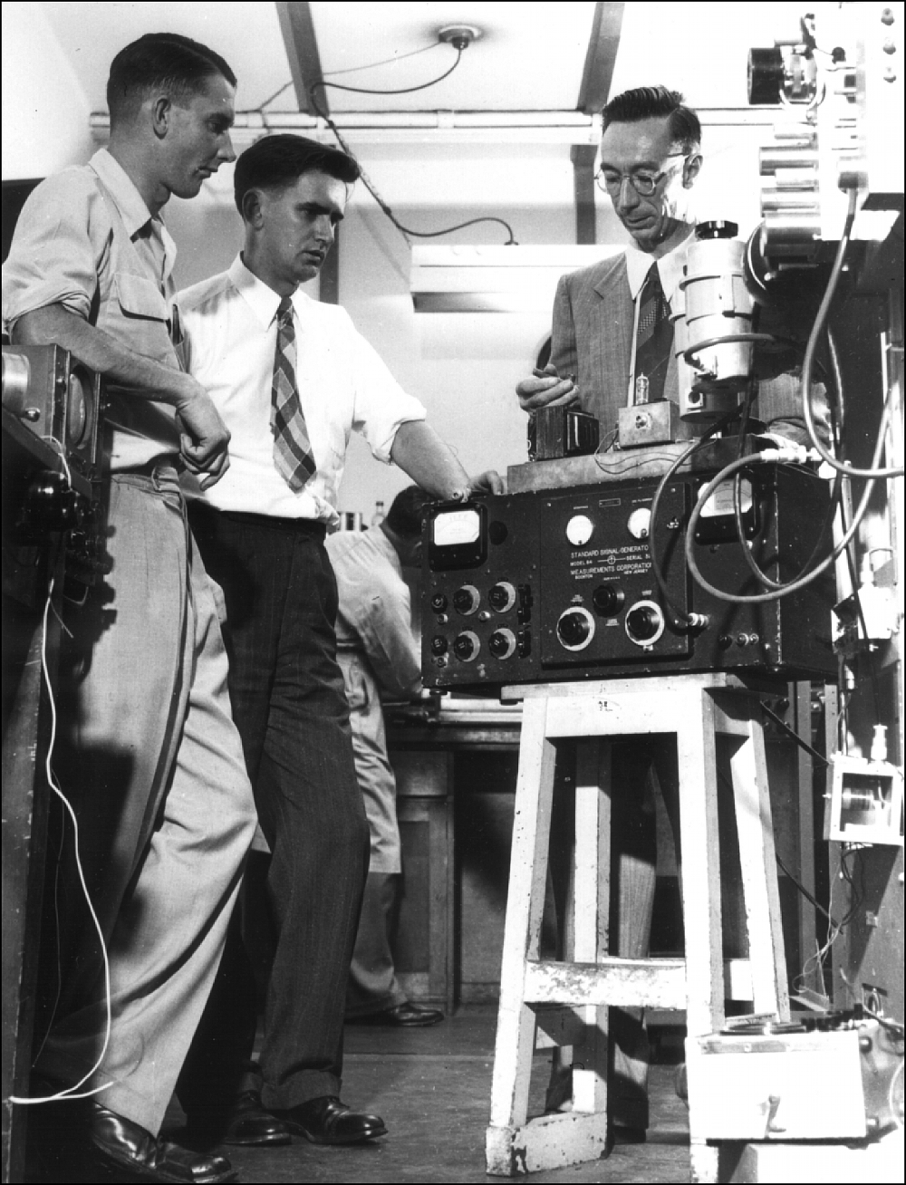 Three men standing near radio equipment in a laboratory in the late 1940s.