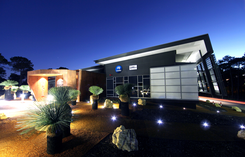 A large modern building, seen at evening, with grass trees near the front entrance.
