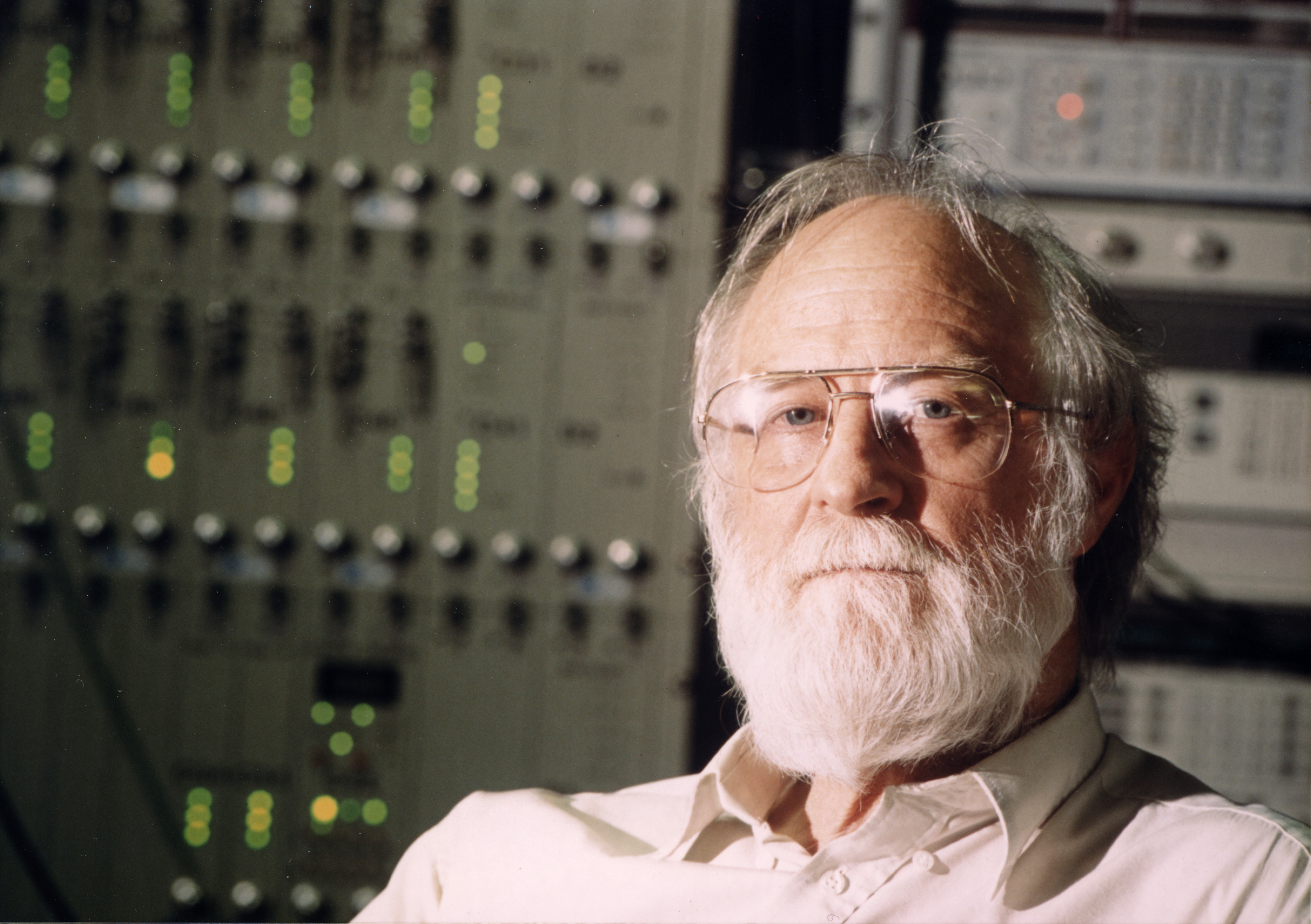 A man with a beard in front of a rack of equipment.