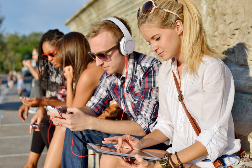 Bench of people using mobile devices