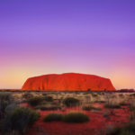 Uluru, a monolithic rock in central Australia, glowing orange at sunset.
