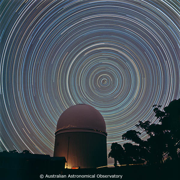 Star trails - bright concentric circles in the night sky - with a dome-shaped building in the foreground.