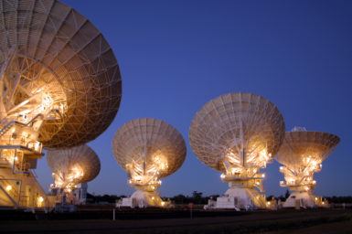 Five white radio telescope dishes point to the night sky, the dishes are illuminated