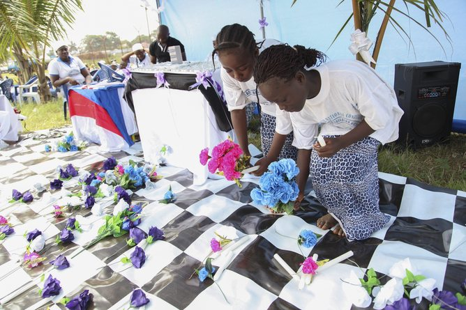 Liberian children lay flowers in memory of all Liberians who have died of the Ebola virus. Image: EPA/Ahmed Jallanzo