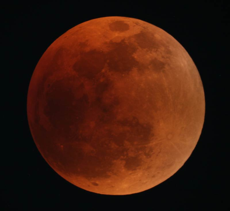 The full Moon, rusty red in colour, and dark sky