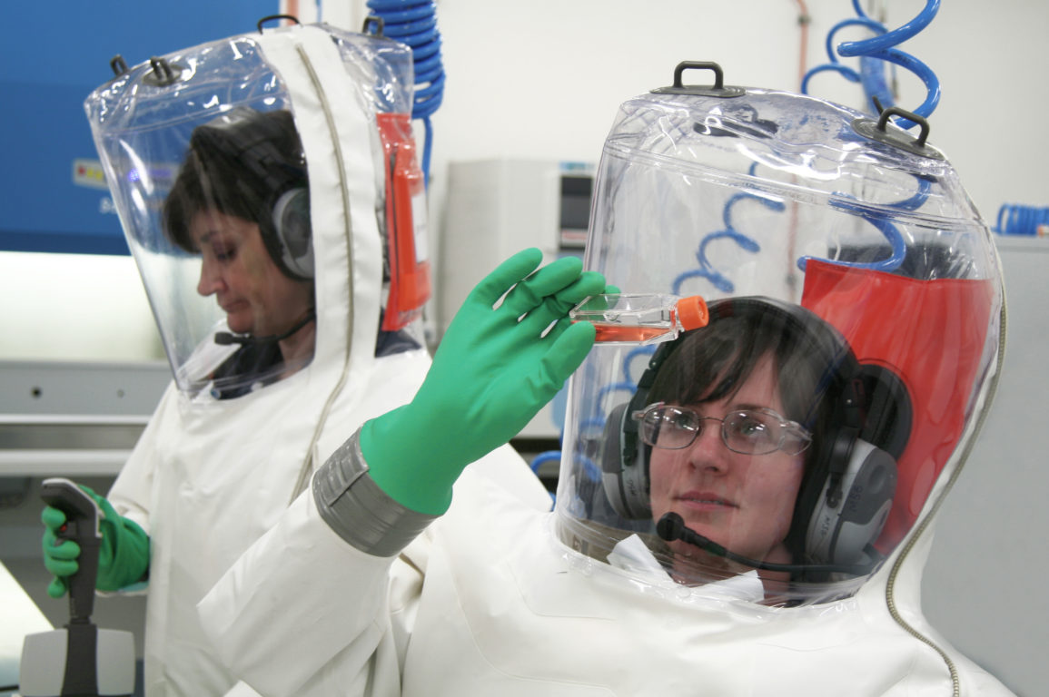 two female scientists conducting experiment in lab, fully suited in fully enlcosed biocontainment suits