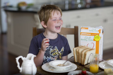 Happy young boy eating bowl of cereal at kitchen table