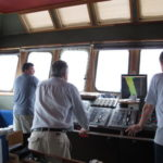 Captain Mike Watson (r) studies the seafloor maps as Colin Woodroffe (middle) looks out to sea (image MNF + Bruce Barker)