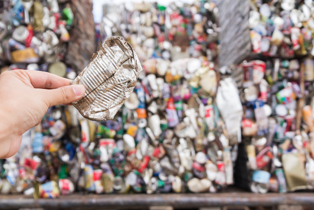 Hand holding crish aluminium drink can in foreground of piles of crushed metal waste