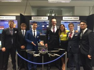 Seven university students stand behind the drone they designed, at an exhibition