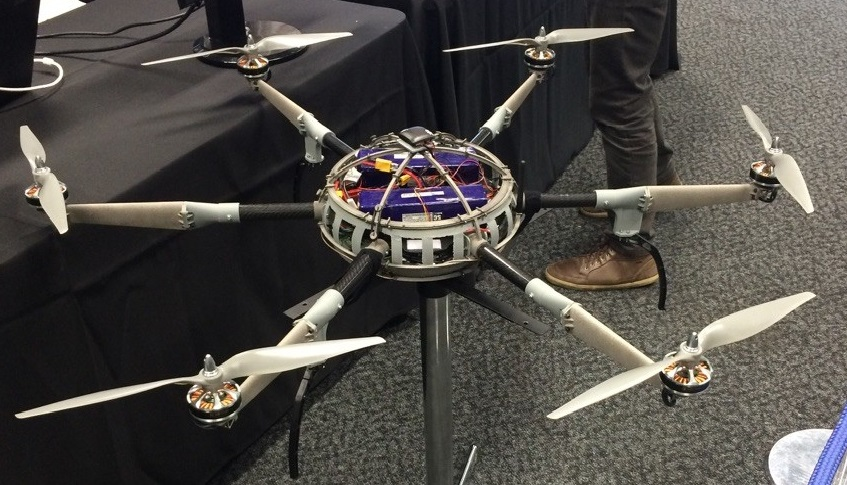 A spherical drone with six arms and propellers sits on a stand at an exhibition