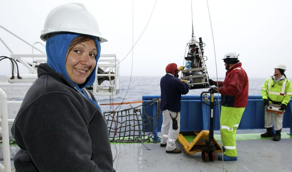 Woman in left of picture wearing jumper and hardhat on boat with scientific equipment hanging from cable background. Ocean, Investigator, Voyages
