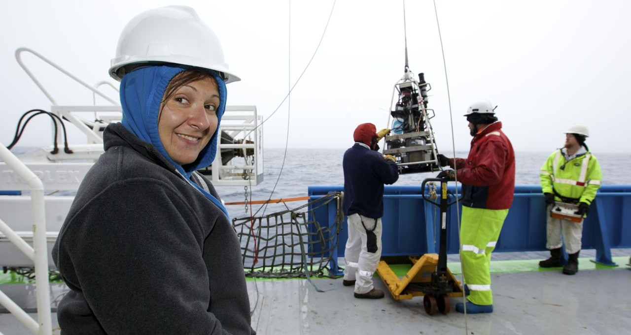 Woman in left of picture wearing jumper and hardhat on boat with scientific equipment hanging from cable in background