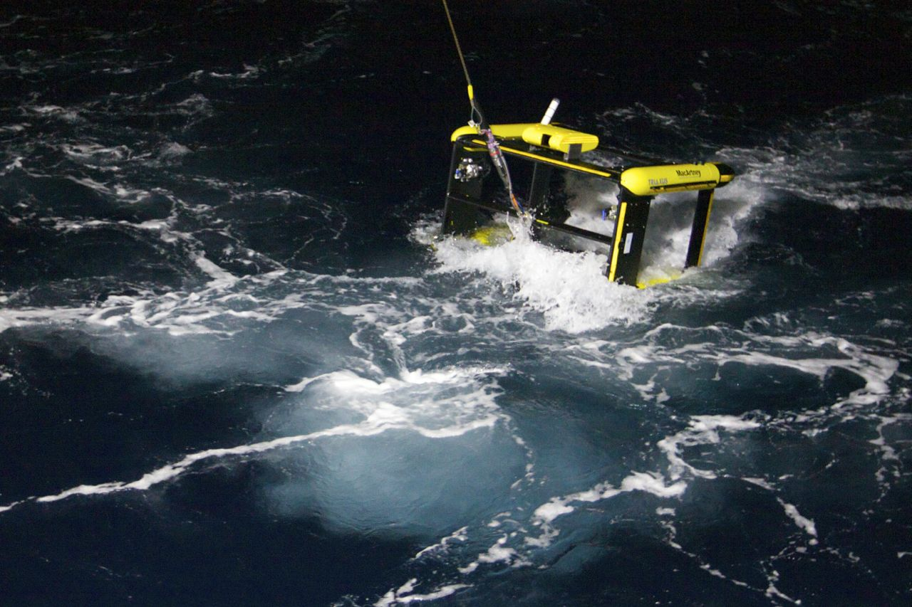 Yellow and black remote controlled vehicle being lowered into ocean at night