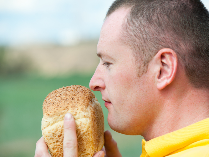 A men smelling a loaf of bread.
