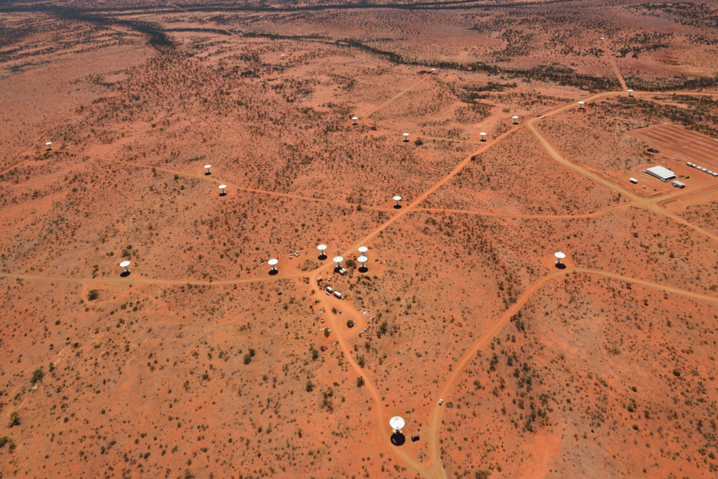 Aerial view of multiple radio telescope antennas connected by roads in the outback.