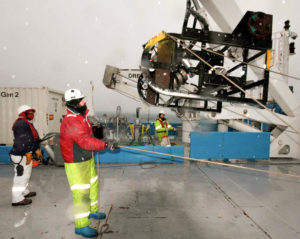 Man wearing red jacket and yellow high vis pants guiding equipment suspended above deck of boat