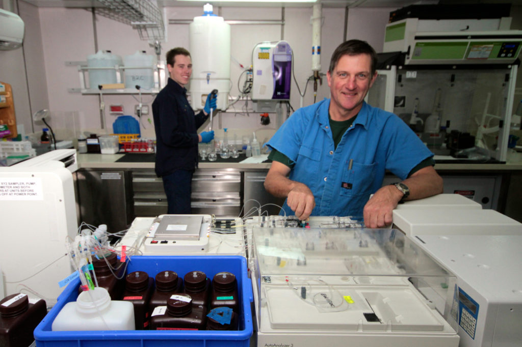 Two people wearing blue in laboratory looking at camera