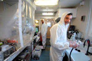Two people wearing white clean suits in clean lab environment