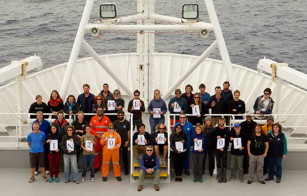 Group of people standing together holding pieces of paper on ship