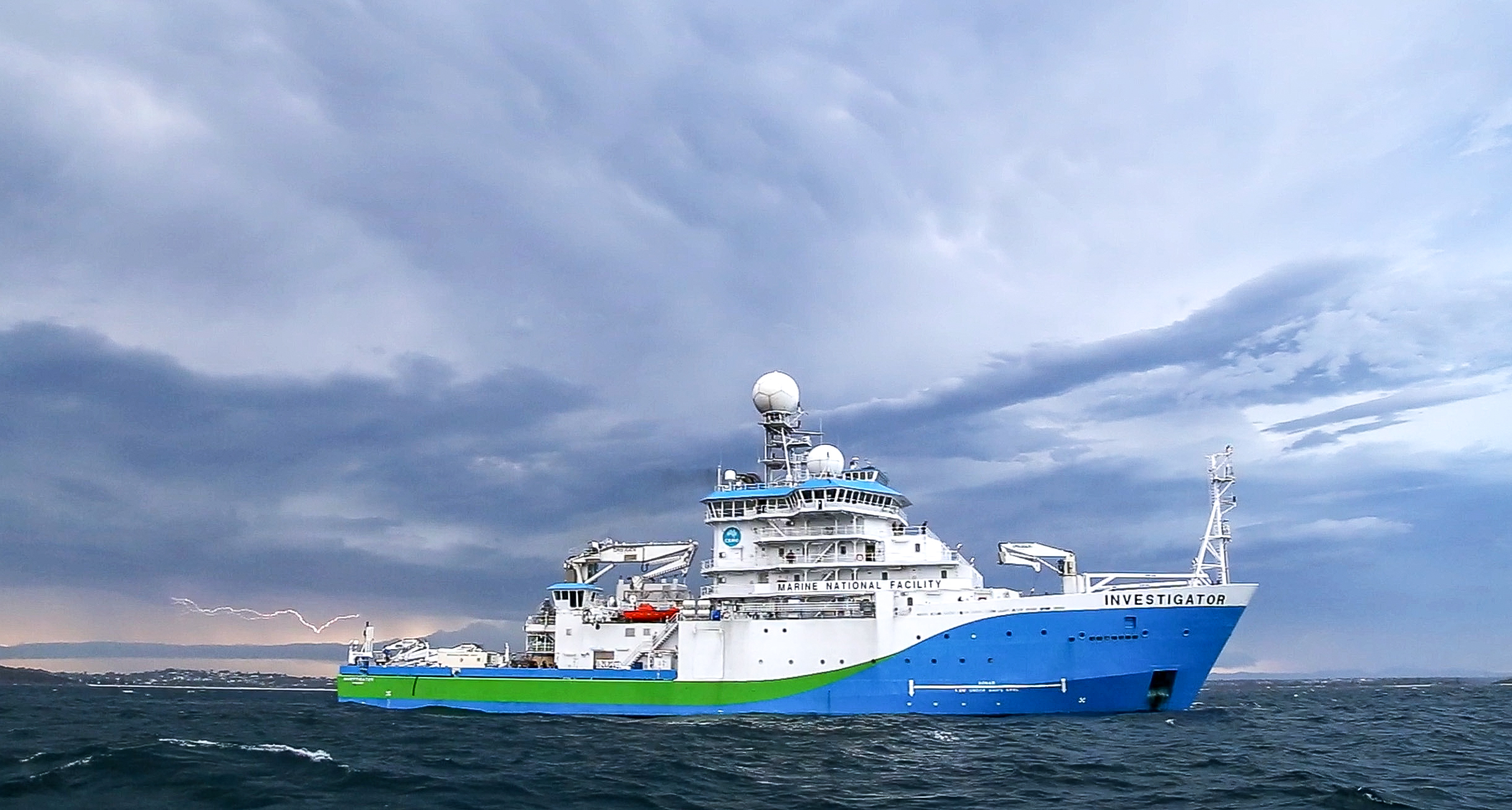 Ship with Green and blue markings in ocean with lightening bolt in background