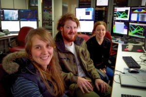 Shipboard operations room where acoustic and other data are monitored, edited, quality controlled, and visualised. Watchstanders: University of Tasmania PhD student Sally Watson (left), University of Tasmania graduate Nic Polmear (center), and Australian National University graduate Anna Bradney (right). Credit: Pete Harmsen.