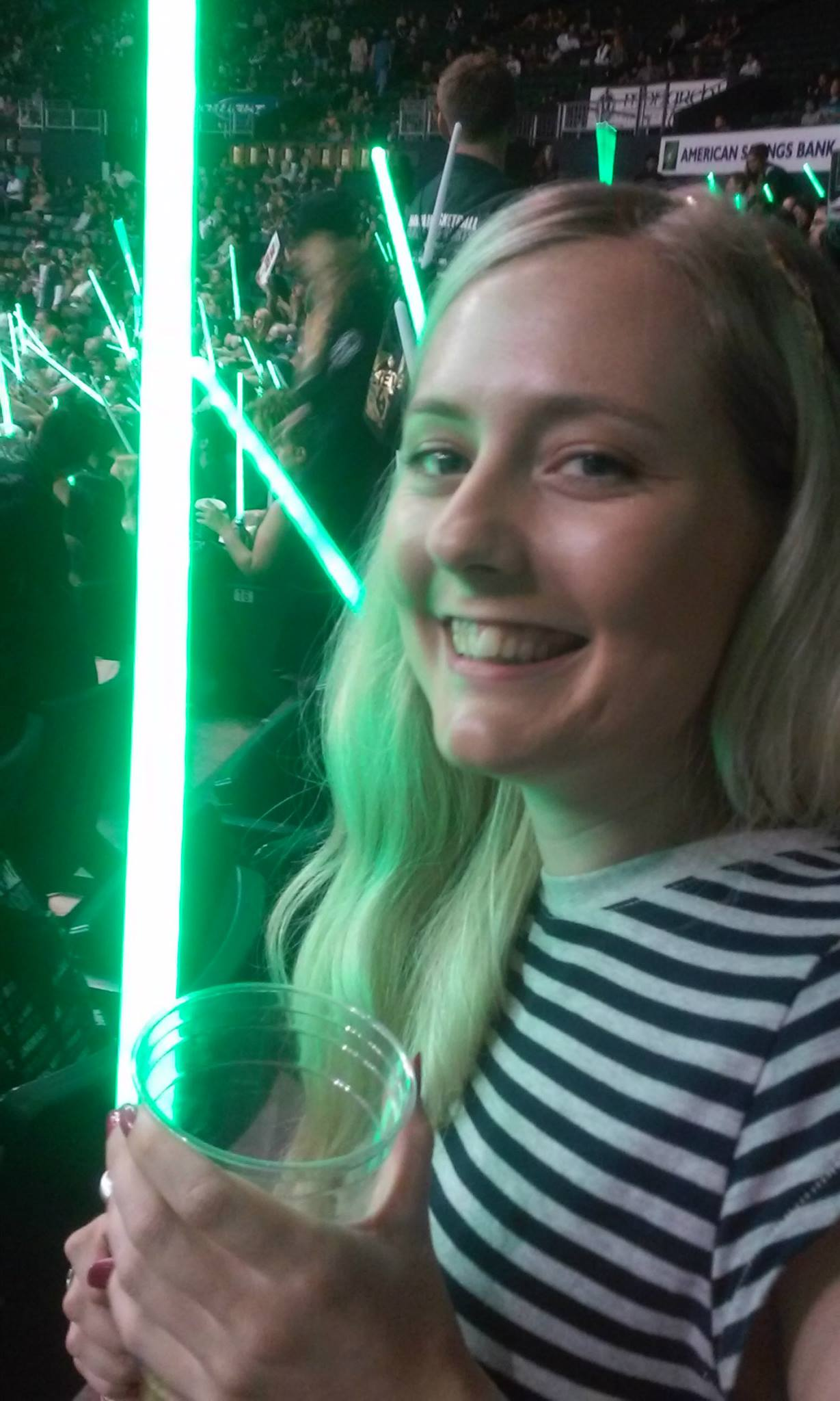 Ellen Singleton holding lightsaber at basketball game