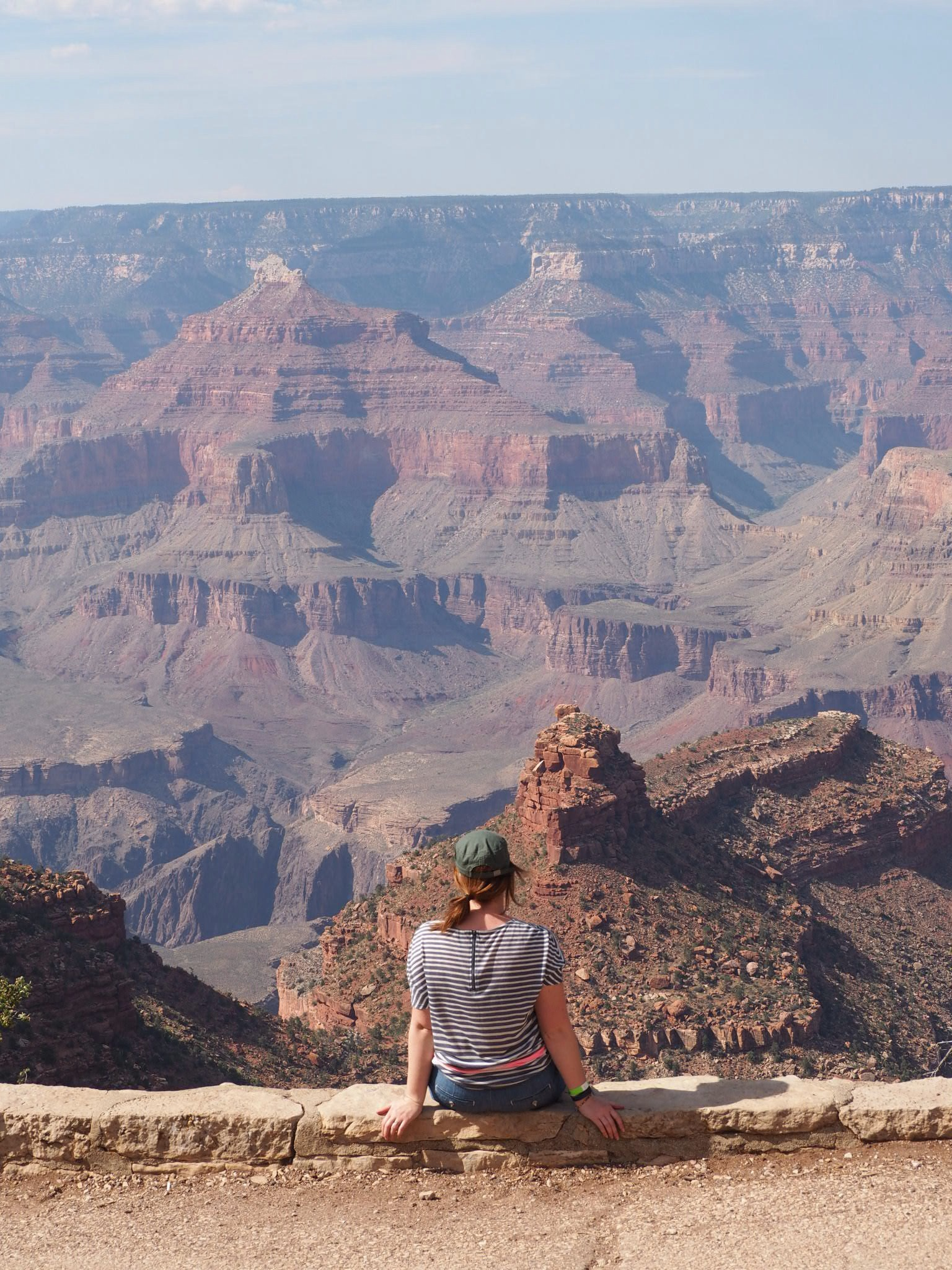 Emma Pyers with back to camera, looking out on Grand Canyon