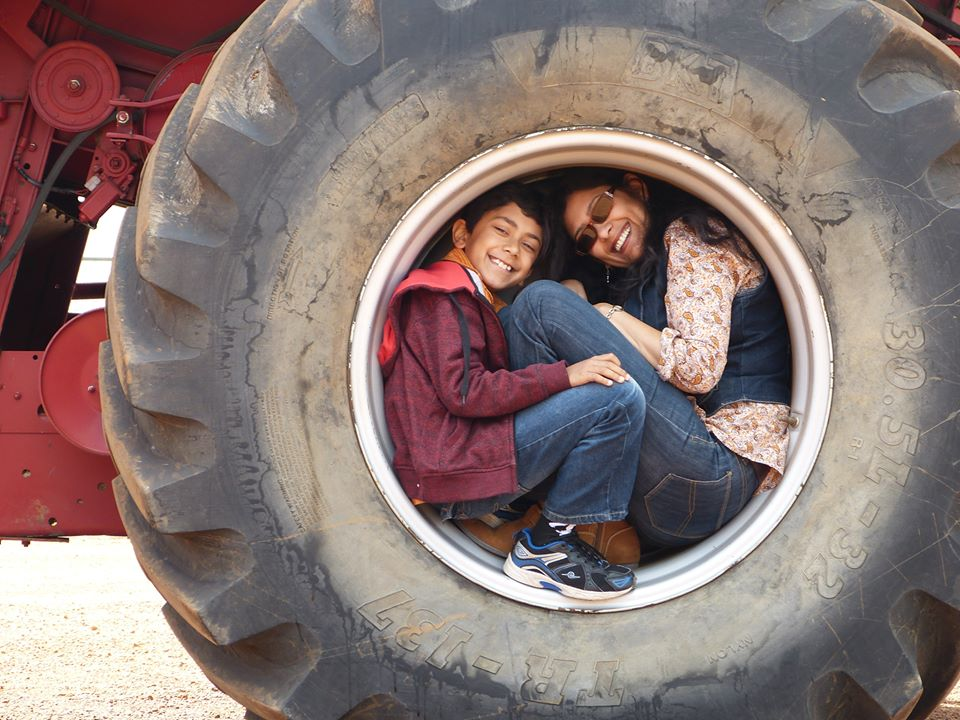 Soma Chakraborty squeezed into a tyre, with a young boy