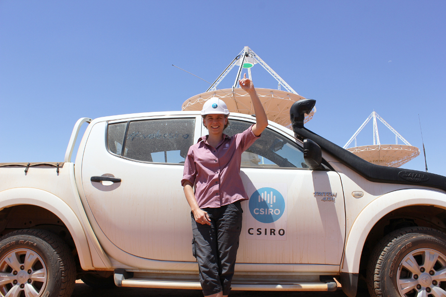 Dr Lisa Harvey-Smith leaning against a car and pointing to the sky with an ASKAP telescope behind.
