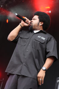 Man standing holding microphone in right hand wearing black shirt