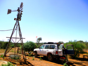 A 4 wheel drive field research vehicle parked near a water windmill in the outback of Australia