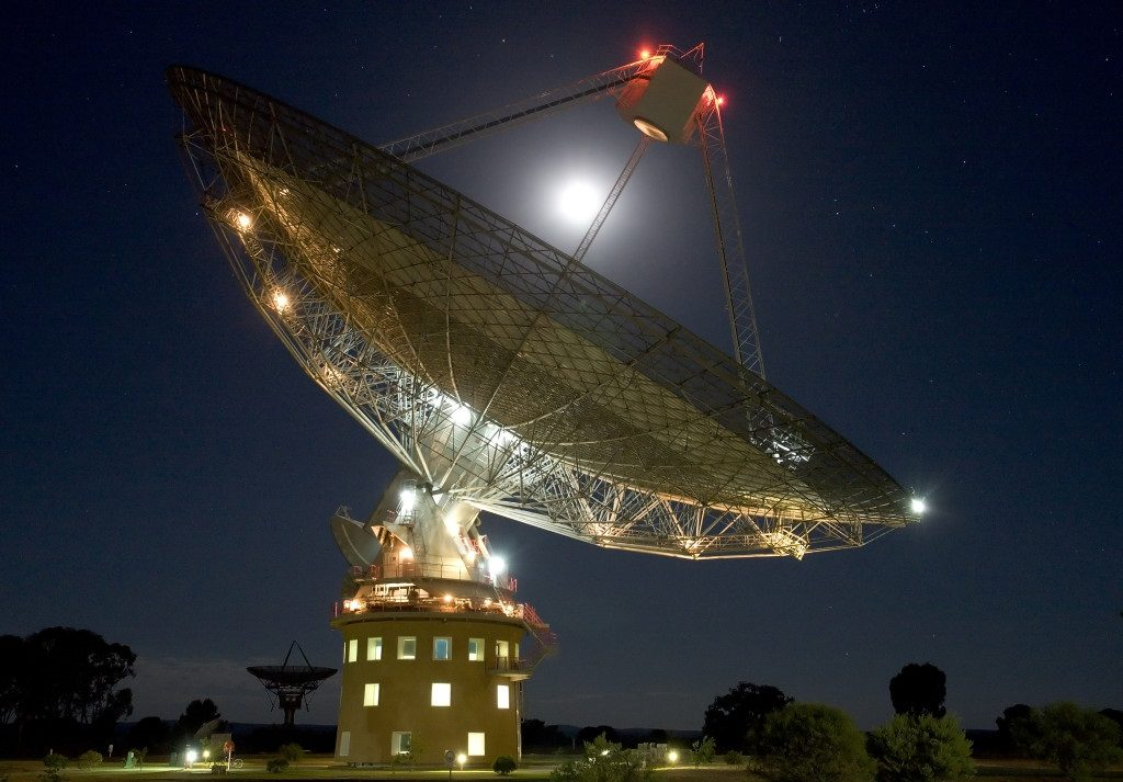 An almost full moon shines brightly above our Parkes Radio Telescope.