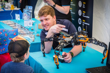 A researcher showing a six-legged robot to a small child at National Science Week