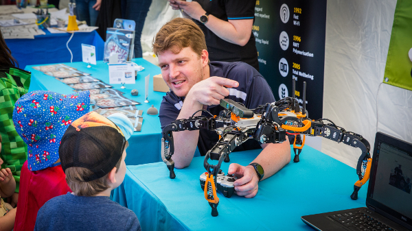 A researcher showing a six-legged robot to a small child