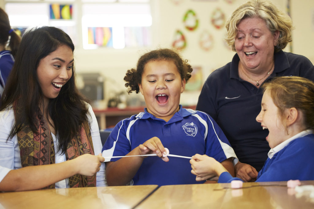 A STEM professional, teacher and two students participating in a science activity