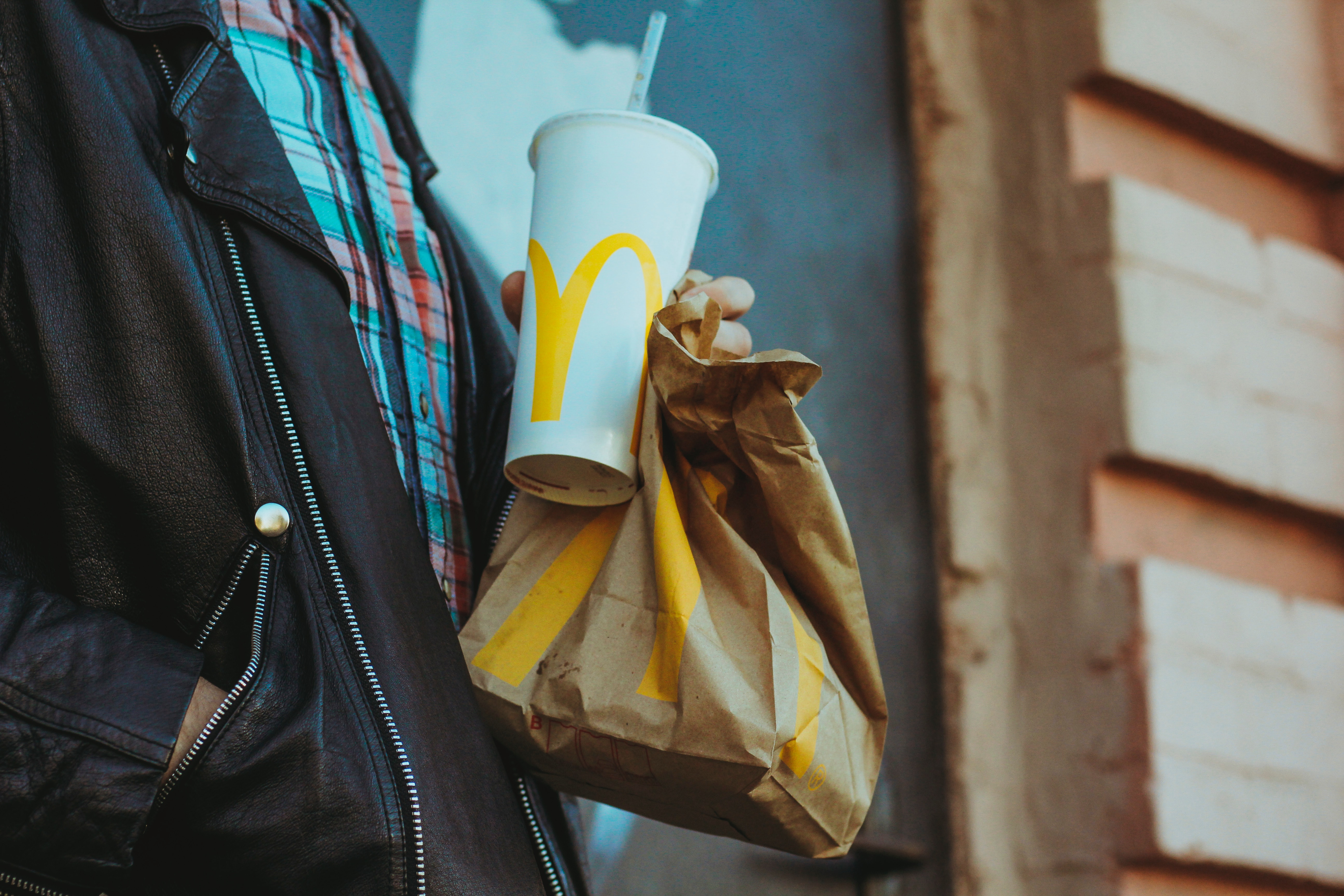 close up of person holding mcdonalds bag and drink cup