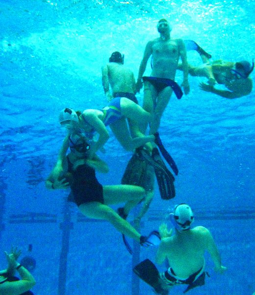 A view from underwater of seven people in a swimming pool playing a game of underwater rugby.