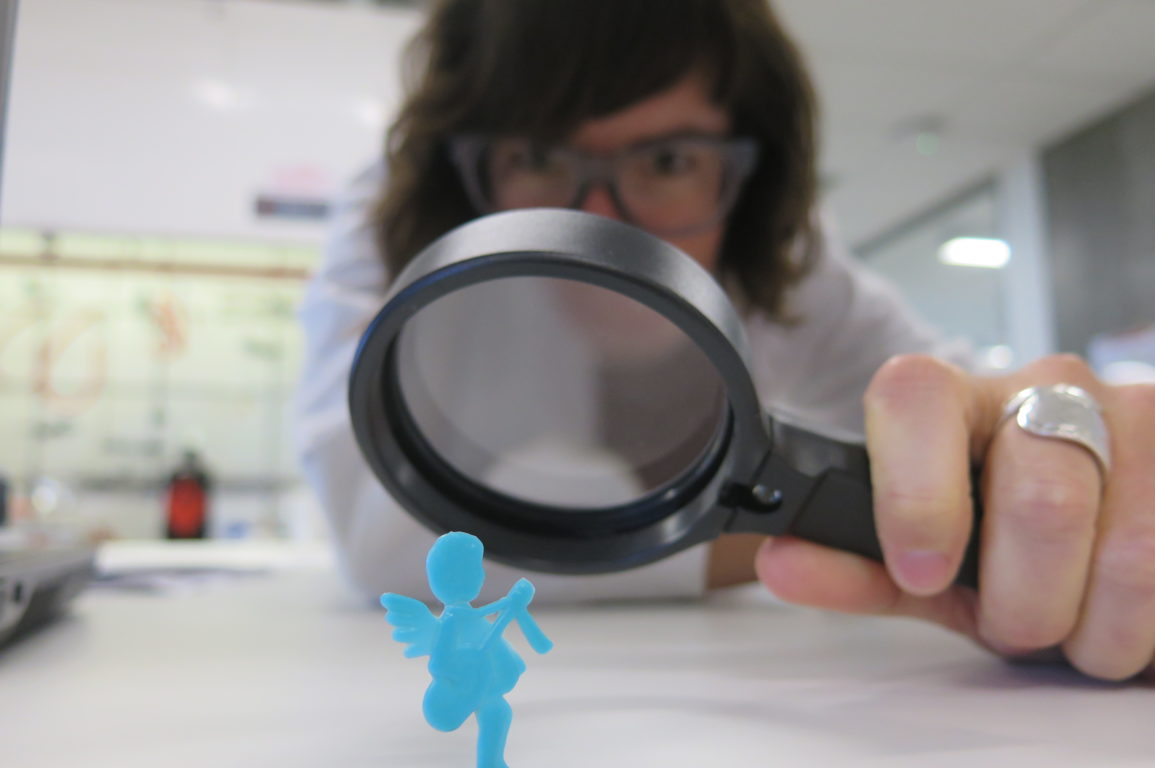 Dr Lucy looking at Polly (who is a plastic toy) through a magnifying glass