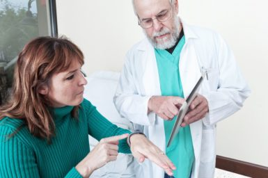 Doctor showing his patient a smart device to help monitor her health. Smart watch fabricated.