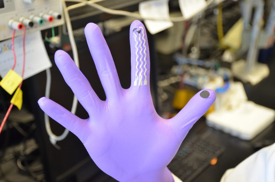 "hand in purple glove, fingers out stretched, three grey ""wave"" lines running down the index finger, black circle on thumb pad. background: blurred computers and cables in a lab setting."