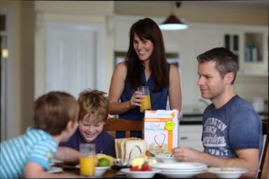Kitchen table with breakfast spread. Mother standing and father seated watching sons.